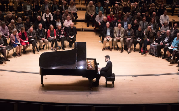 A pianist playing piano in front of a crowd